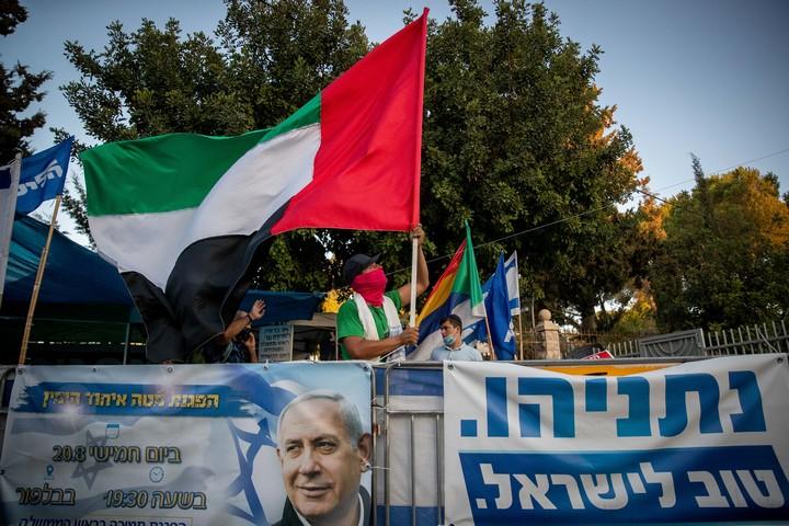 פסקי הלכה תומכים בקשר עם ישראל. מפגין למען נתניהו מניף את דגל האמירויות מול בית ראש הממשלה (צילום: יונתן זינדל / פלאש 90)