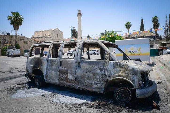 פיתוי התיירות נעשה ללא התייעצות עם התושבים. מכונית שרופה על רקע העיר העתיקה בלוד (צילום: אבשלום ששוני / פלאש 90)