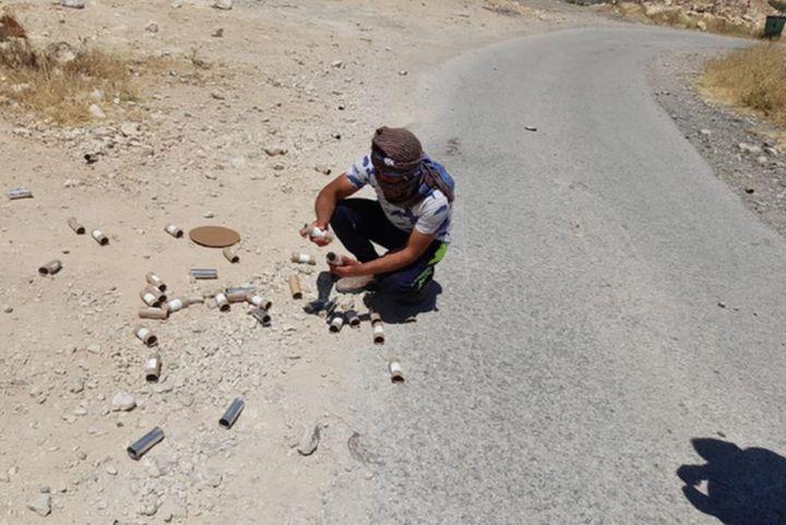 לאיפה שהלכנו, החיילים רדפו אחרינו וירו. פלסטיני אוסף תרמילים בתוואני (צילום: באסל אל עודרה)