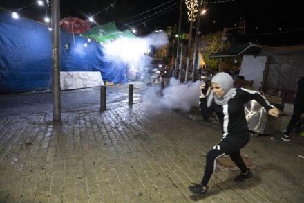 קודם זורקים רימוני הלם, אחר כך חושבים. פלסטינית נמלטת מרימון הלם אתמול בשער שכם (צילום: אורן זיו)