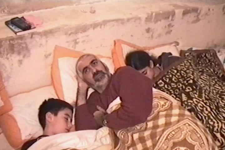 דימה סרוג'י, אחיה ואביה ישנים במרתף ביתם בבית ג'אלה, כדי להתגונן מפני הפצצות ישראליות בזמן האינתיפאדה השנייה (באדיבות דימה סרוג'י)