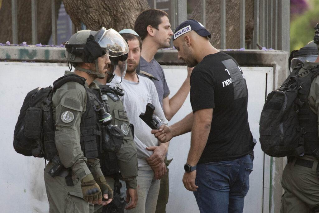 שוטרים מחזיקםי נשק לפעיל ימין בלוד בשבוע שעבר (צילום: אורן זיו)
