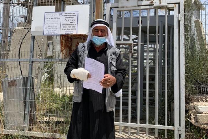 מחמוד חמאמדה מאל מופגרה, שמתנחלים שברו את ידו ביום חמישי, ליד תחנת המשטרה בקריית ארבע (צילום: באסל אל-עדרה)