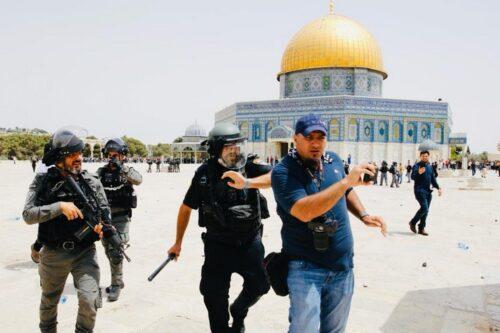 שוטר מכה את צלם סוכנות הידיעות הצרפתית אחמד ע'ראבלי, במתחם מסגד אל אקצה, ב-21 במאי 2021 (צילום: סלימאן חאדר)