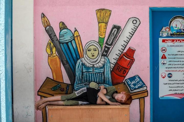 """המולת אדם, לכלוך בכל מקום, אין טיפת פרטיות, המוני משפחות ישנות אחת על השינה בכיתות לימוד קטנות. ילד בבית ספר של אונר""""א בעזה, אליו נמלט עם משפחתו (מוחמד זאנון / אקטיבסטילס)"""