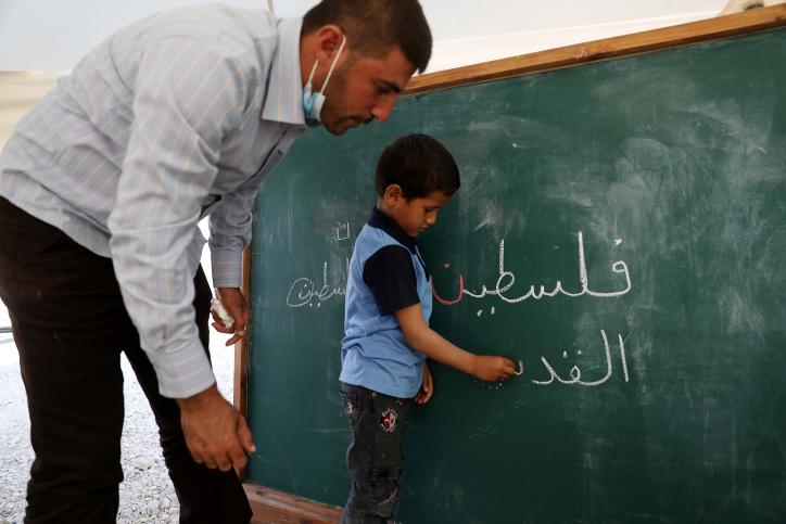 """הפלסטינים רוצים קודם כל לתקן את העוול. ילד פלסטיני כותב """"פלסטין"""" על הלוח (צילום: ויסאם השלאמון / פלאש 90)"""