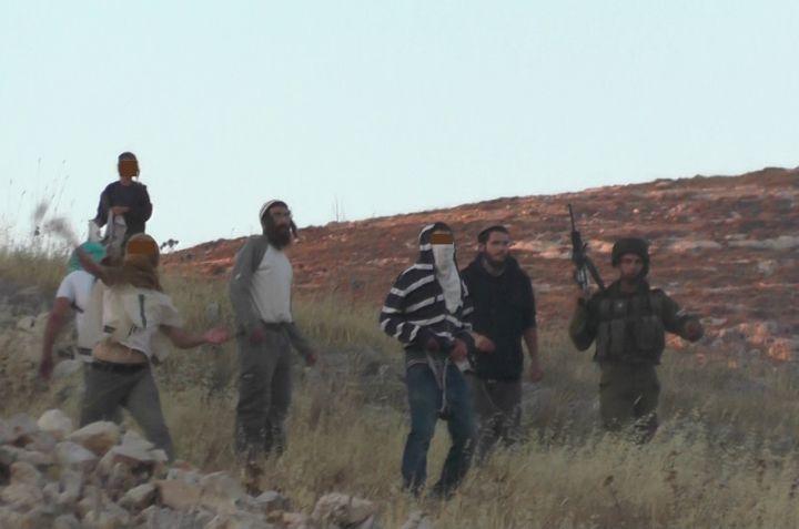 מתנחל רעול פנים מיידה אבן לעבר תושבי בורין, חייל עומד מנגד: תיעוד מתוך התקיפה בבורין (צילום: מוניר קאדוס, יש דין)