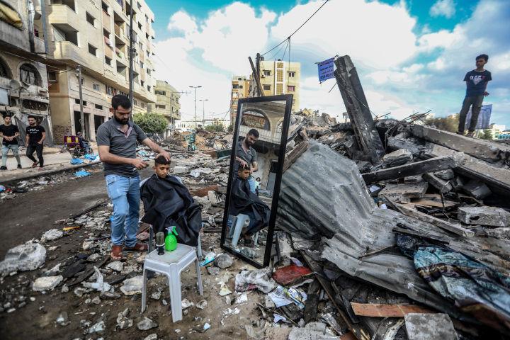 הספר האשם אל-ג'רושה עובד בתוך הריסות המספרה שלו (צילום: מוחמד זאנון / אקטיבסטילס)
