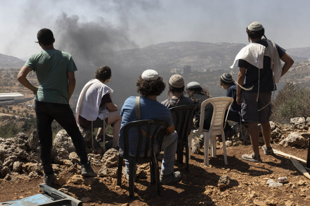 הרצון של הצבא לפנות את מאחז אביתר נובע מהמאבק של תושבי ביתא. פעילי ימין באביתר משקיפים על העשן העולה מכיוון ביתא (צילום: אורן זיו)