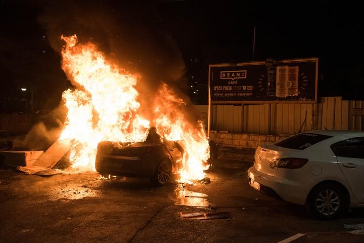מכונית עולה באש בזמן המהומות בעכו, ב-12 במאי 2021 (צילום: רוני עופר / פלאש90)