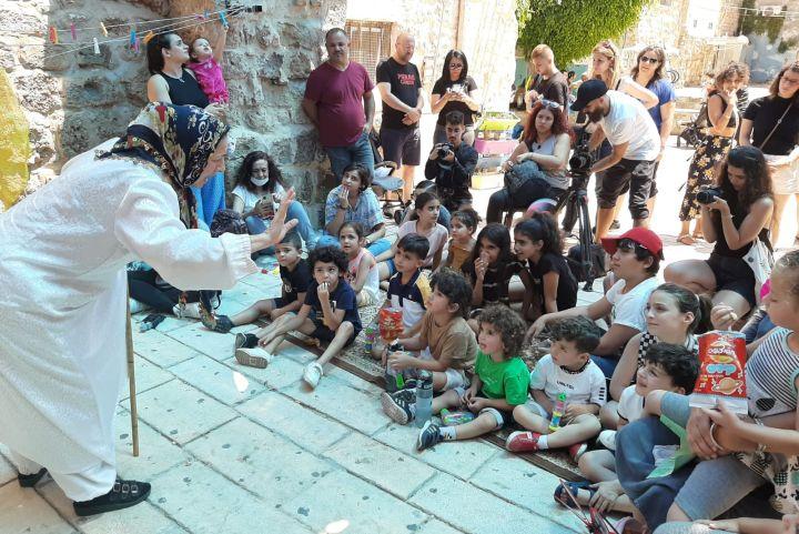 """""""הילדים לא יודעים מי אנחנו, מה התרבות שלנו"""". רימא סוליאמן בכרי מופיעה בפני ילדים בעכו העתיקה (צילום: סוהא עראף)"""