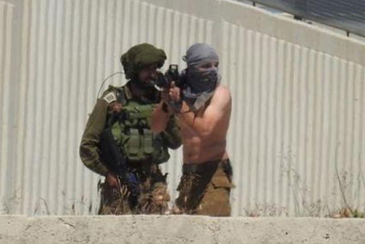 המתקפות התחילו באותה שעה במקומות שונים בגדה. רעול פנים עם קצין בדרגת סרן בעוריף, באזור שבו נהרג פלסטיני מאש חיה (צילום באדיבות מאזן שחאדה)