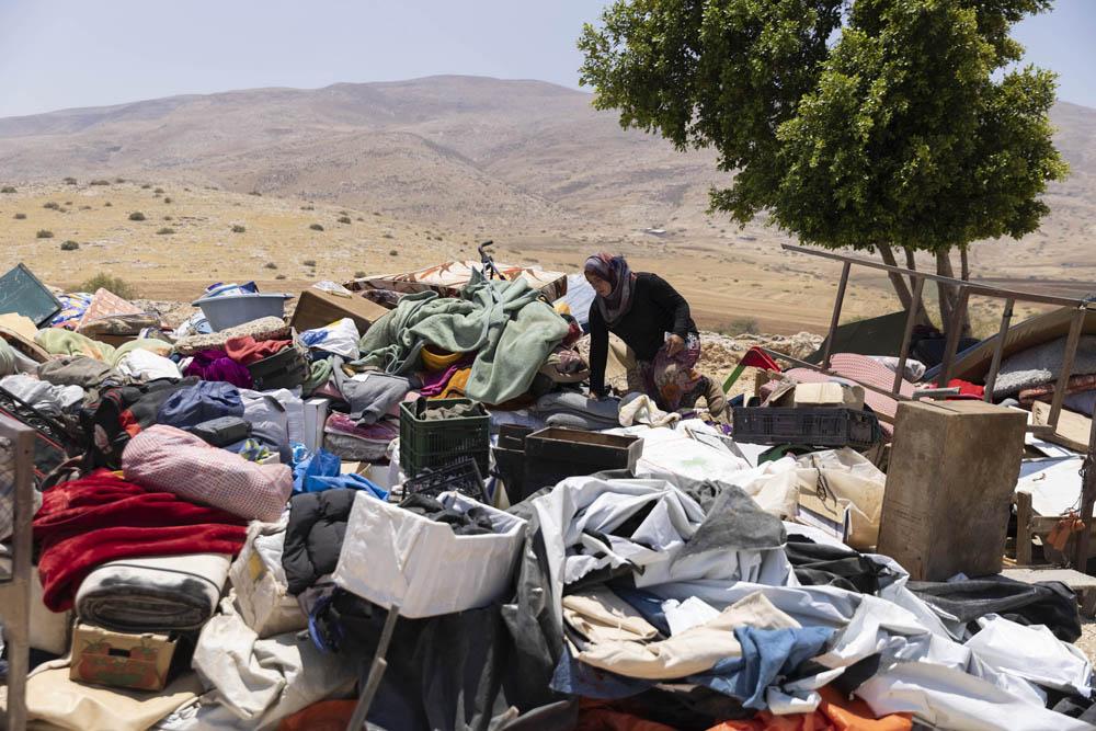 """תושבת ח'רבת חומסה נוברת בחפצים האישיים שהצבא החרים במהלך פינוי הישוב אתמול והשליך במרחק יותר מ-10 ק""""מ מהמקום המקורי (צילום: אורן זיו)"""