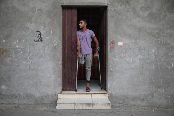 """אדם סאלם בביתו בפתח ביתו במחנה שאטי בעזה. """"רוצה ללכת כמו כולם"""" (צילום: מוחמד זאנון)"""