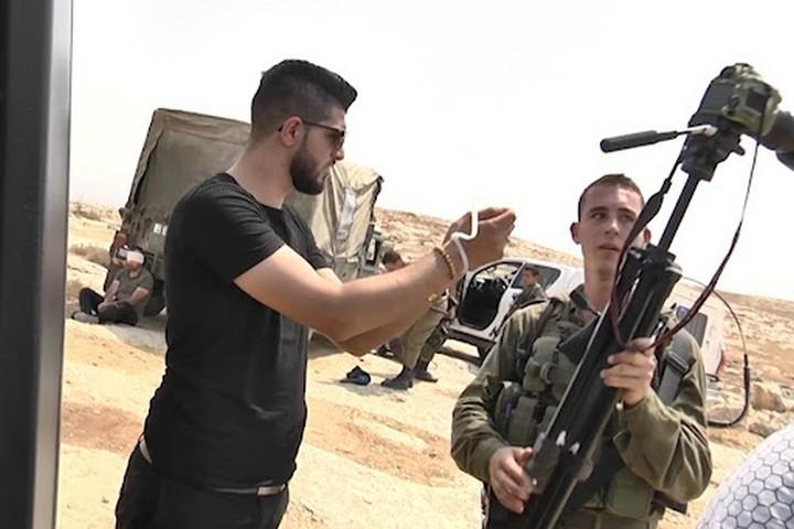 חייל אוזק ולוקח את המצלמה מאיהאב עלאמי, עיתונאי שכותב בסוכנות הידיעות שיהאב. ברקע עיתונאי נוסף, אזוק, שעיניו כוסו (צילום: מאמון וזוז)