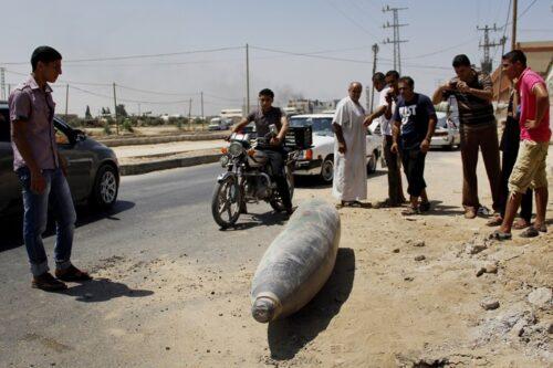 פלסטינים בוחנים טיל ישראלי שלא התפוצץ בעזה, ב-1 באוגוסט 2014 (צילום: מוסטפה אשקר / פלאש90)