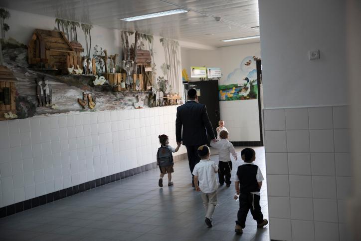 הטיפול בילדים נופל במידה רבה עם הגברים. גבר חרדי מביא את ילדיו לתלמוד תורה בביתר עלית (צילום: נתי שוחט / פלאש 90)