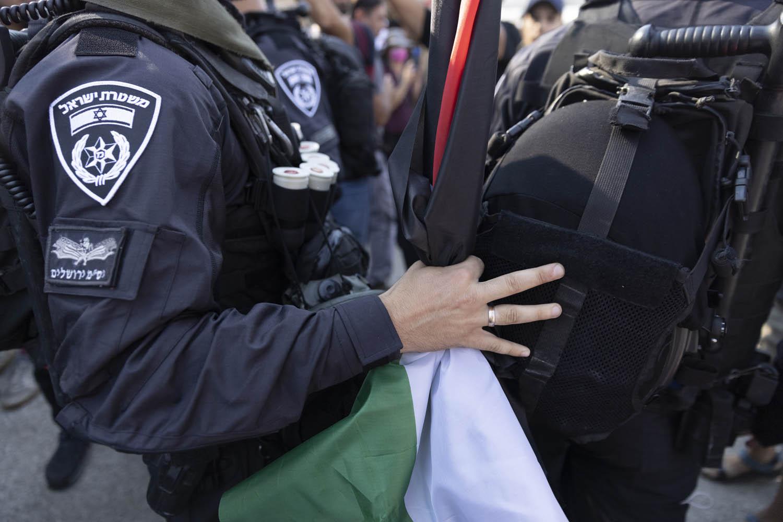 שוטרים מחרימים דגלי פסלטין במהלך מחאה בשייח׳ ג׳ראח, 30 ביולי 2021 (צילום: אורן זיו)