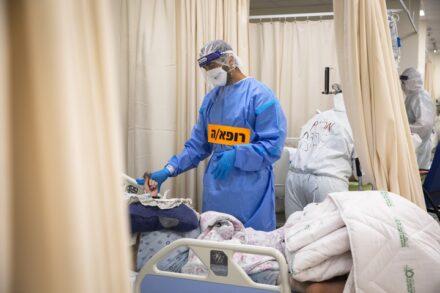 רופא מטפל בחולה במחלקת קורונה (צילום: אוליבייה פיטוסי / פלאש90)