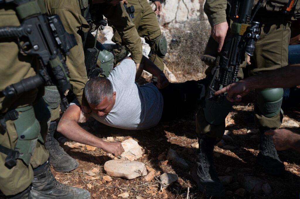 החקלאים הפלסטינים חוששים להגיע לאדמות ללא ליוו. חיילים עוצרים את מוחמד ח'טיב במהלך מסיק בסלפית (צילום: מתן גולן)